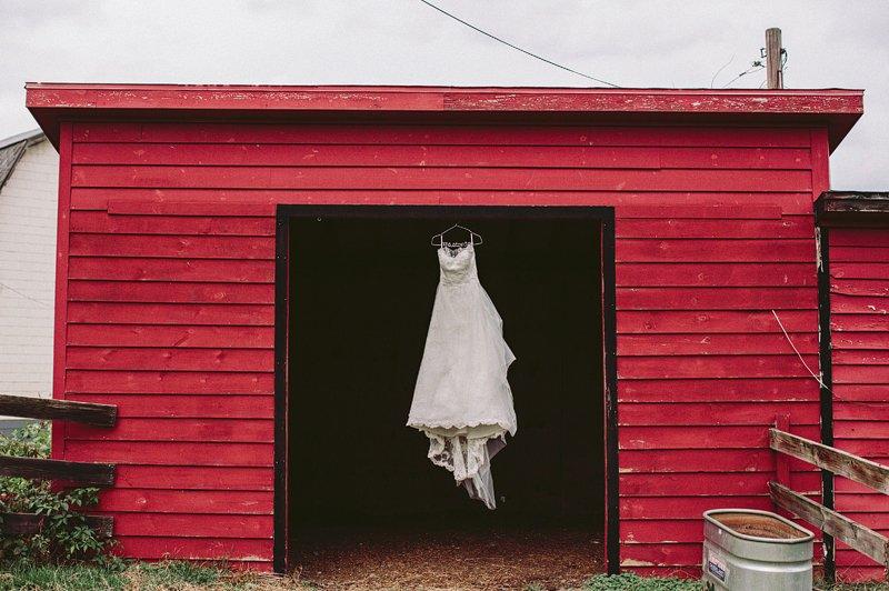 Wedding dress hanging in barn