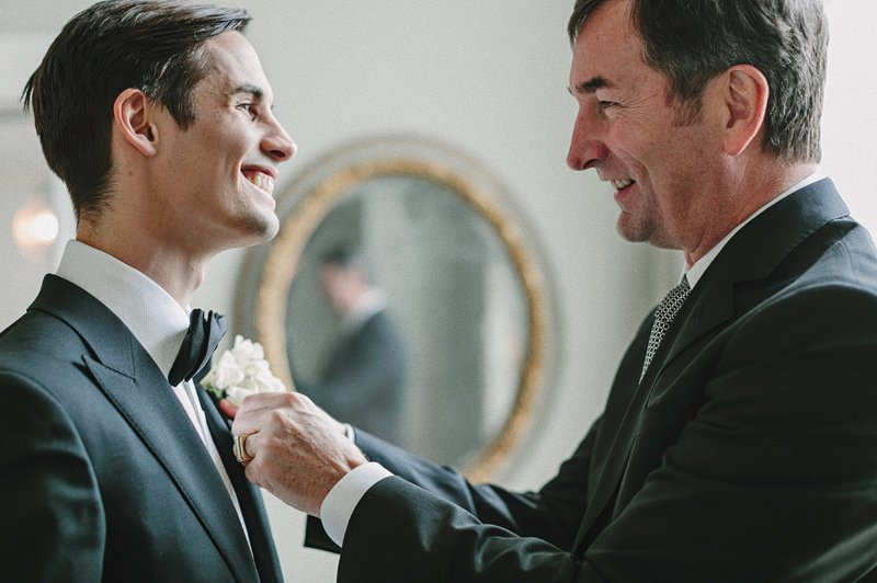 father putting on groom's boutonniere